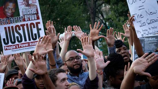 Protesters raise their hands up during a peaceful demonstration in New York