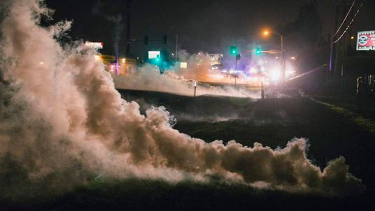 Tear gas rises from the ground after having been fired upon protesters who are continuing to react to the shooting of Michael Brown, in Ferguson, Missouri