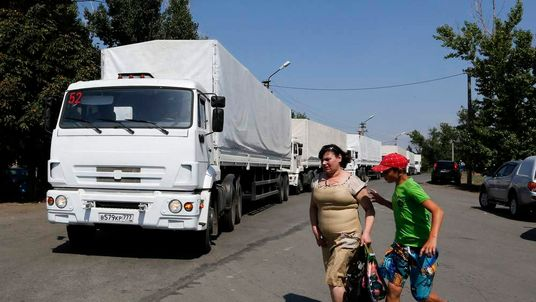 A woman and a boy walk near trucks of a Russian convoy carrying humanitarian aid for Ukraine near a Russia-Ukraine border crossing point in Rostov Region