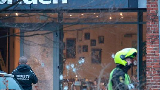Police presence is seen next to damaged glass at the site of a shooting in Copenhagen