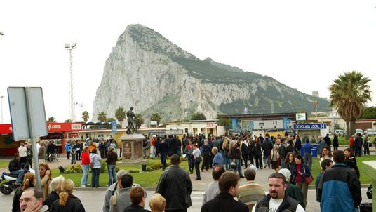 PEOPLE WAIT TO CROSS THE BORDER INTO GIBRALTAR.