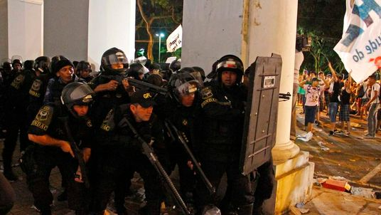 Police protect themselves against stone-throwing demonstrators during an anti-government protest in Belem