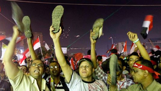 Anti-President Mohamed Mursi protesters hold up their shoes after a speech by Mursi, at Tahrir Square in Cairo