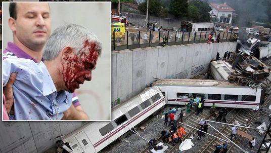 Rescue workers pull victims from a train crash near Santiago de Compostela
