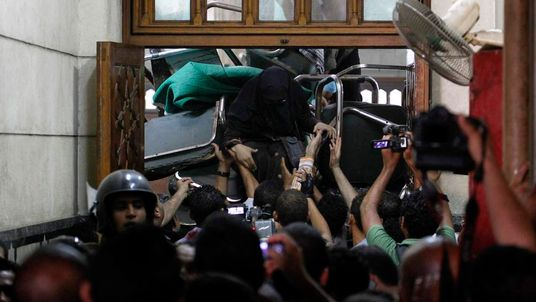 A woman climbs from behind a barricade set up by supporters of deposed Egyptian President Mohamed Mursi inside the al-Fath mosque in Cairo