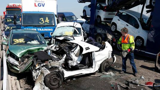 A rescue worker stands amongst the wreckage of some of the 100 vehicles involved in multiple collisions, which took place in dense fog during the morning rush hour, on the Sheppey Bridge in Kent, east of London