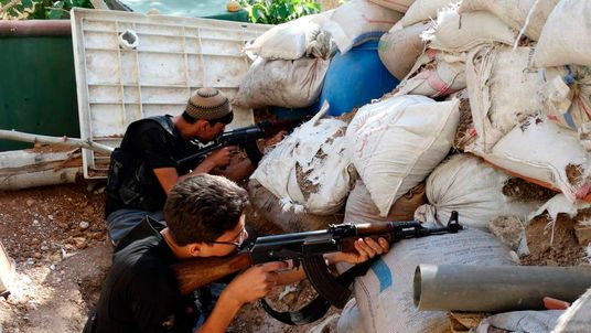 Free Syrian Army fighters take up positions behind piled sandbags as they aim their weapons in the eastern al-Ghouta, near Damascus