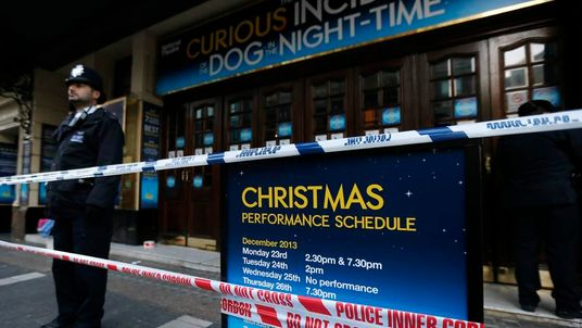 Police officers stand on duty outside the Apollo theatre on the morning after part of it's ceiling collapsed on spectators as they watched a performance, in central London