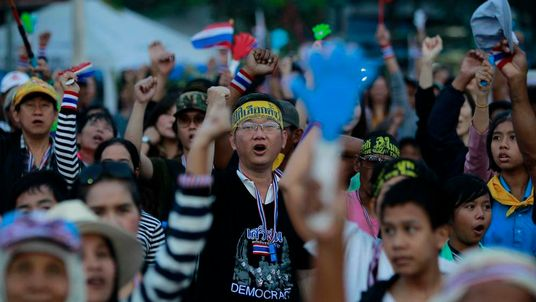 Anti-government protesters sing the national anthem during their rally at the Democracy Monument in central Bangkok