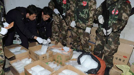 Police check crystal meth seized in a raid on Boshe village in China.