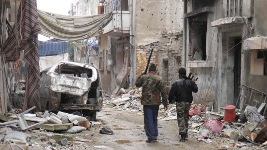 Free Syrian Army fighters walk past damaged buildings and vehicles in the besieged area of Homs
