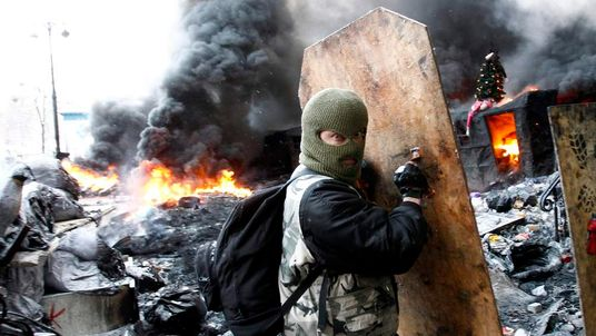 A pro-European integration protester takes cover behind a makeshift shield at the site of clashes with riot police in Kiev