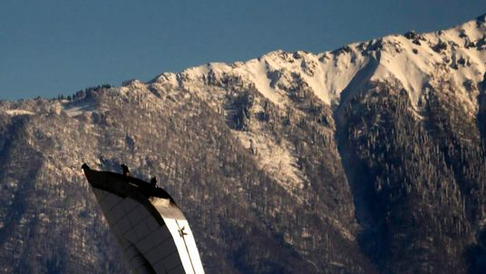 Workers stand atop of the Olympic torch in front of Caucasus Mountain at the Olympic Park in the Adler district of Sochi
