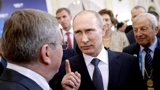 Russian President Putin talks with IOC President Thomas Bach, at a welcoming event for IOC members in Sochi