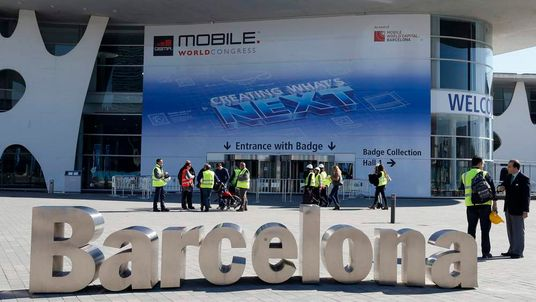 Workers walk past a Mobile World Congress entrance in Barcelona