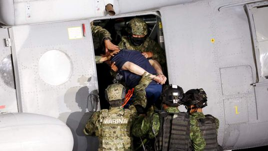 "Soldiers escort drug lord Joaquin ""El Chapo"" Guzman into a helicopter"