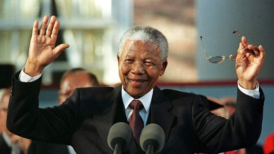 South Africa's President Nelson Mandela raises his hands to quiet the crowd during a prolonged stand..
