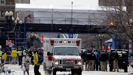 A runner is escorted from the scene after explosions went off at the 117th Boston Marathon in Boston