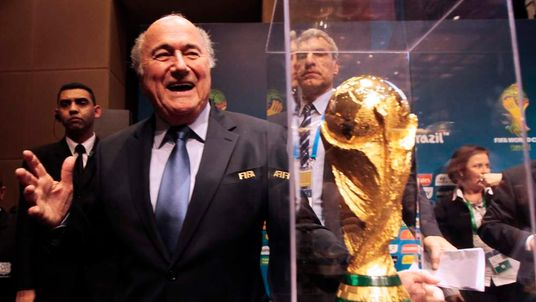 FIFA President Sepp Blatter gestures next to the World Cup trophy after a media conference in Sao Paulo.