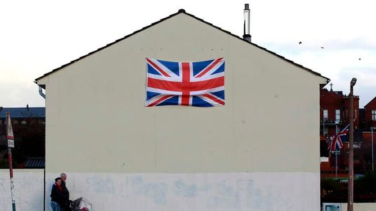 People walk past a house displaying a Union flag in the Shankill Road area of West Belfast