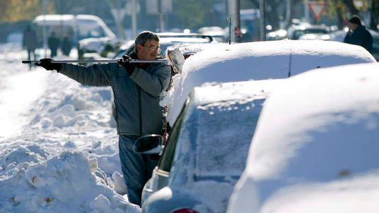 A man removes snow on a car in Zagreb
