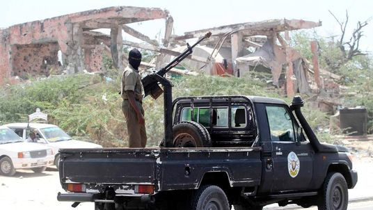 Member of Somali security forces stands on top of a truck mounted with a weapon as he patrols the streets during an operation against suspected militant Islamist group al Shabaab in Mogadishu