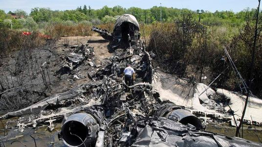 A NTSB official looks over the wreckage of a Gulfstream IV private jet at Hanscom Airfield in Bedford