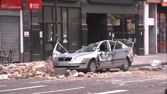 A woman died after part of a building fell on a car in Holborn, central London