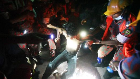 A survivor is pulled from the wreckage of a building that collapsed in Dhaka, Bangladesh.