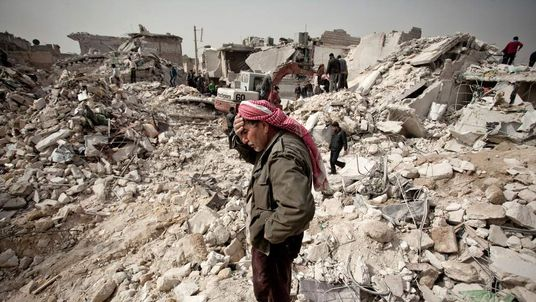 A man stands in the rubble of his house in Aleppo