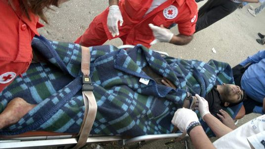 An injured Syrian man is wheeled on a stretcher by Lebanese Red Cross medical personne