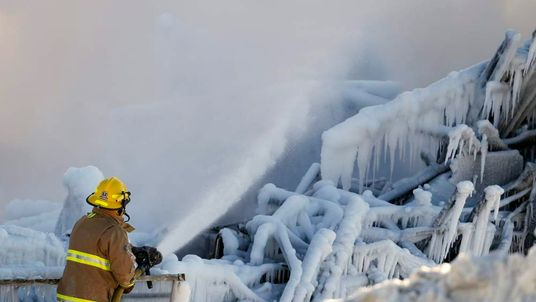 A firefighter sprays water at the Residence du Havre after a fire in L'Isle Verte, Quebec