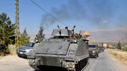 Lebanese army soldiers flash victory signs while riding on armoured carriers and military vehicles as they advance towards the Sunni Muslim border town of Arsal