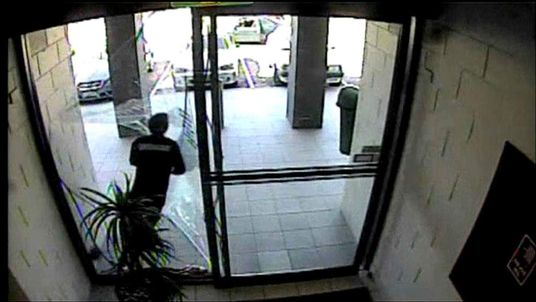 Bungling shopping centre thief runs through glass door.