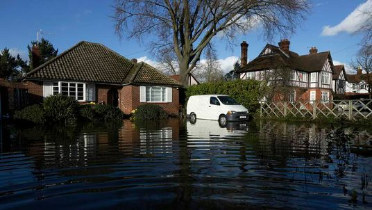 Homes and vehicles are surrounded by flood water after the river Thames flooded the village of Wraysbury, southern England