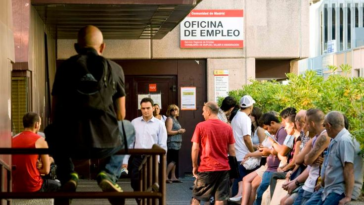 Unemployed workers wait outside a job center in Spain