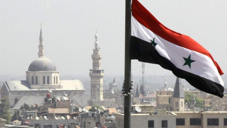The Syrian flag flutters above Damascus