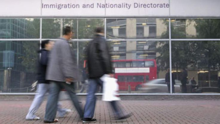 People walk past the Immigration and Nationality Directorate