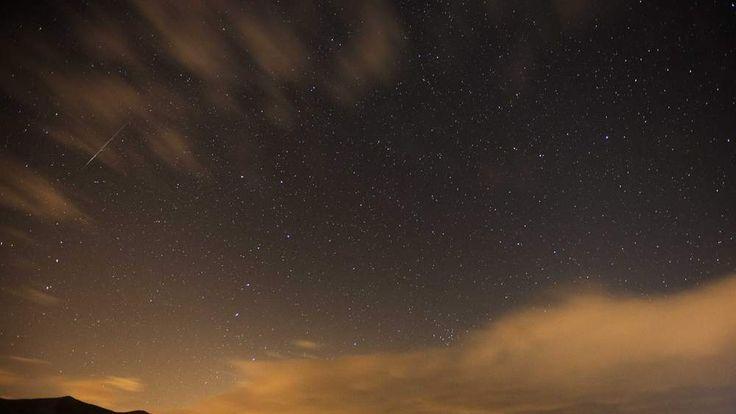 Geminid meteor streaks are seen above the Judean desert near the Israeli Kibbutz of Ein Gedi