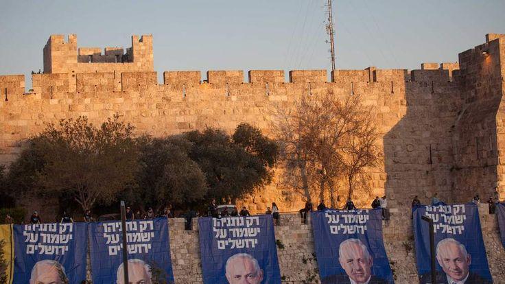 Likud party activists hang campaign posters of Israeli Prime Minister Benjamin Netanyahuunder David's Citadel at Jaffa Gate in the old city of Jerusalem