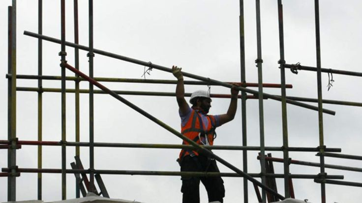 A worker takes down scaffolding on a construction site in London