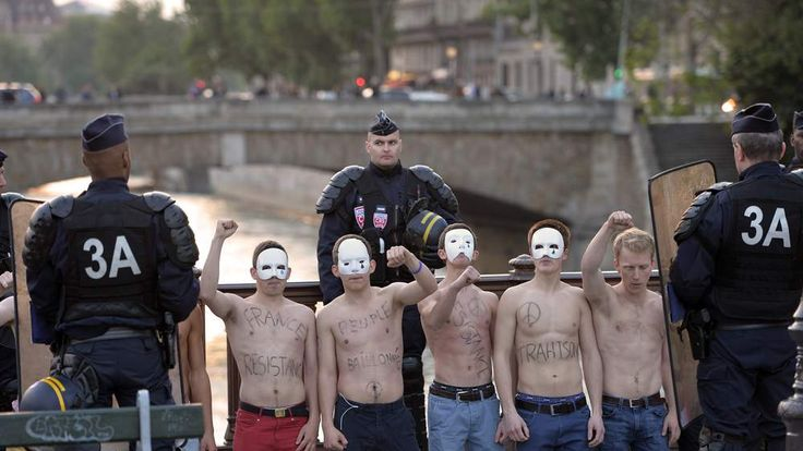 Riot police stand around bare-chested men wearing white masks and belonging to an anti-gay group (Hommen), as they demonstrate against a bill legalizing same sex marriages