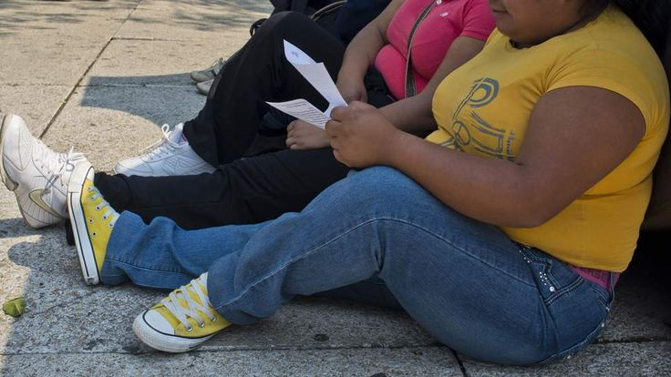 A woman sits on a pavement in Mexico City