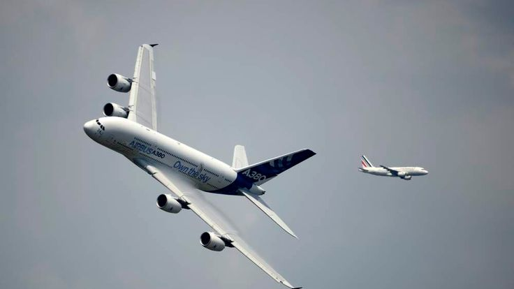 An Airbus A 380 (L) aircraft flies over Le Bourget airport on June 17, 2013 on the opening day of the International Paris Air show