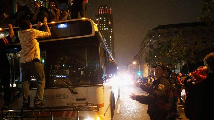 Rioters climb a city bus