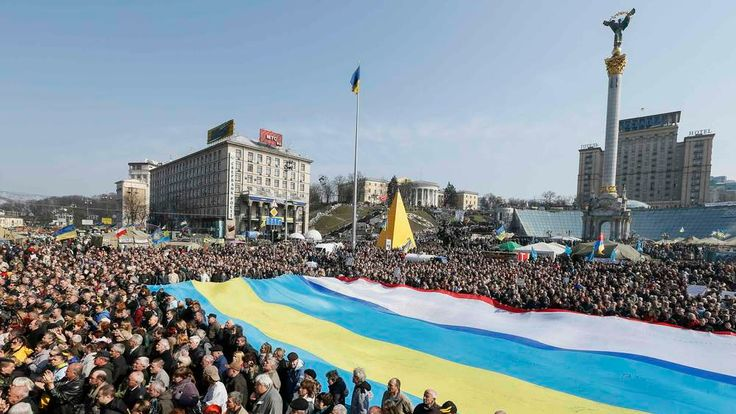People hold a huge flag depicting multiple flag colours during an anti-war rally at Independence Square in Kiev