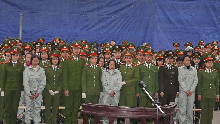 Defendants, all drugs smugglers, flanked by police stand and listen to their verdicts after a two-week long trial held by a local People's Court inside a jail in the Northeastern province of Quang Ninh