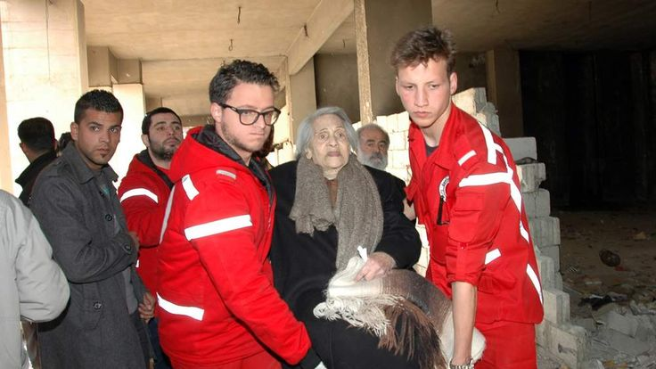 Syrian Red Crescent workers help civilians to be evacuated from besieged parts of the Syrian city of Homs