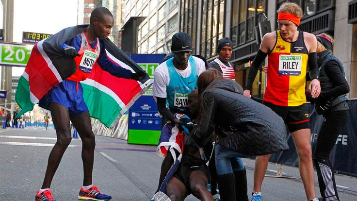 Mo Farah of Great Britain collapses at the finish line in the arms of Stephen Sambu of Kenya (C) and his wife Tania