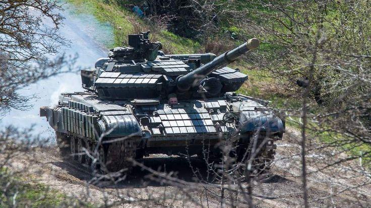 A Russian tank rolls outside a former Ukrainian military base in Perevalnoye, near the Crimean capital Simferopol